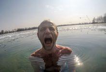Muž v ľadovej vode s grimasou od chladu